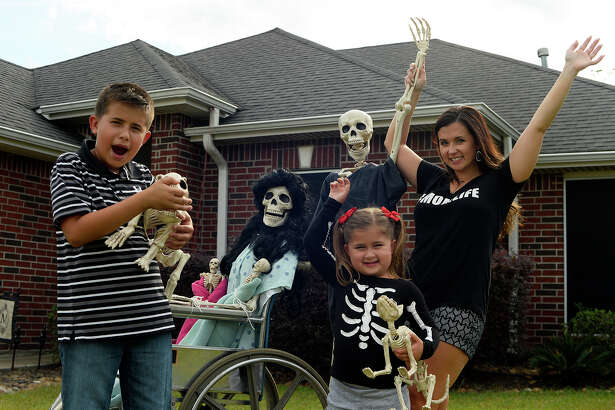 "Amy B. Moses and her children, Macy, 4, and Canon, 10, set up a new scene with the skeleton family in their Lumberton yard every day. Fans can follow the Bones family on her Facebook page ""Keeping up with the Bones.""  Photo taken Wednesday 10/19/16 Ryan Pelham/The Enterprise"
