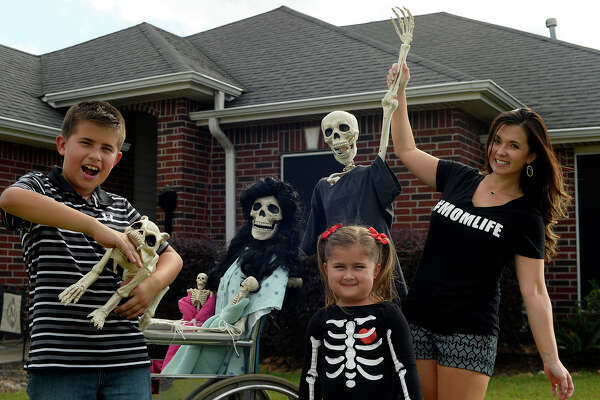 """Amy B. Moses and her children, Macy, 4, and Canon, 10, set up a new scene with the skeleton family in their Lumberton yard every day. Fans can follow the Bones family on her Facebook page """"Keeping up with the Bones.""""  Photo taken Wednesday 10/19/16 Ryan Pelham/The Enterprise"""