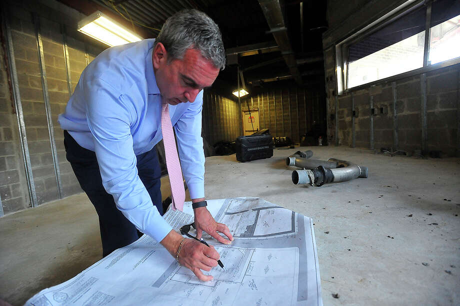 """Tom Broussard discusses the plans he envisions for the former Capital One motor bank building on Fannin Street in the heart of downtown. The site is undergoing cleaning and construction as part of the """"Repurposed Living Project,"""" and will eventually become his home. It sits adjacent to the building in which his great-grandfather had a livery business, making it especially valuable when it became available to purchase last year. Broussard says repurposing the building into a single family dwelling was welcomed by the city and downtown development as part of the move toward revitalization of the downtown area. Photo taken Wednesday, October 19, 2016 Kim Brent/The Enterprise Photo: Kim Brent / Beaumont Enterprise"""