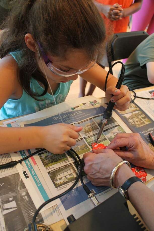 Resident Ally Colavecchio learns how to solder during last year's Innovation Day event. Photo: Contributed Photo