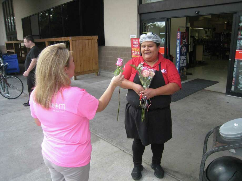 Mitzi Vaughn hands flowers to Elsy Hernandez at the H-E-B in Kingwood during the Petal it Forward initiative from Va Va Bloom in Kingwood and Cleveland Wednesday, Oct. 19. Photo: Jennifer Summer