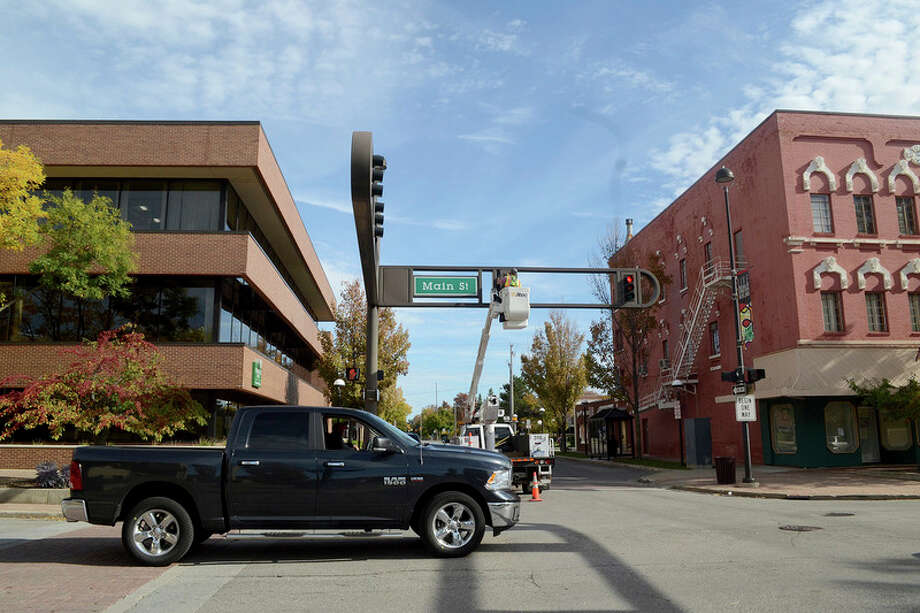 Signs and signals crews on Wednesday, Oct. 19, check to see whether the city's standard signal covers fit downtown fixtures. Chris Aldridge | caldridge@mdn.net