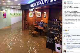 An image of a man in Hong Kong sitting undisturbed by flooding at a Starbucks was posted to TV Most's Facebook page Oct. 19, 2016. Since then, the photo has gone viral.