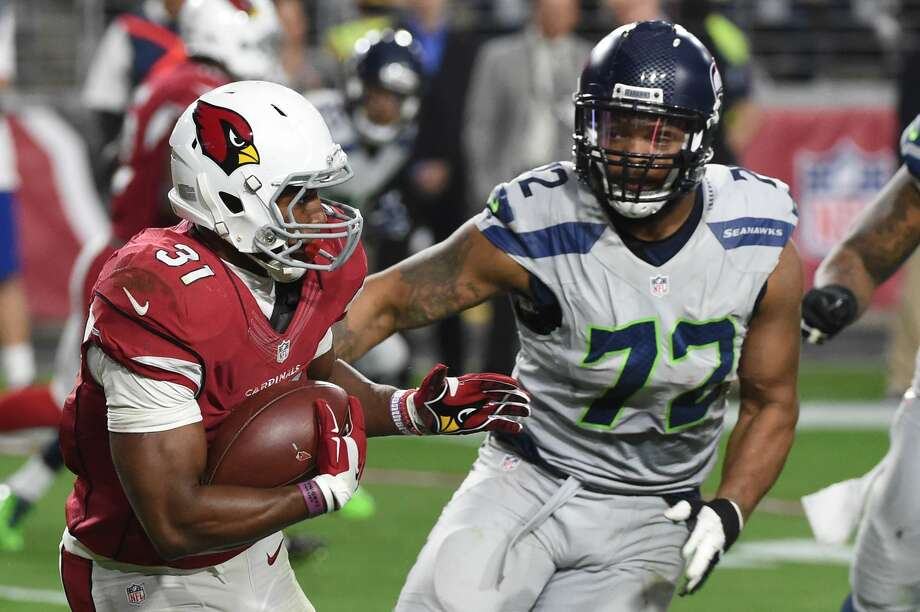 Running back David Johnson of the Arizona Cardinals carries the football in front of defensive end Michael Bennett of the Seattle Seahawks at University of Phoenix Stadium on January 3, 2016 in Glendale, Arizona. Photo: Norm Hall/Getty Images