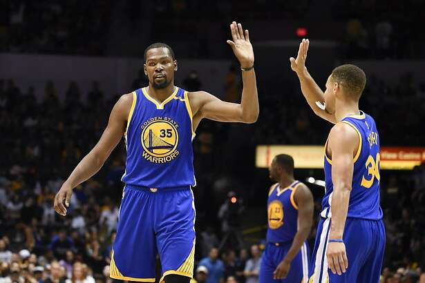 Golden State Warriors forward Kevin Durant, left, high-fives Stephen Curry (30) during the second half of an NBA preseason basketball game against the Los Angeles Lakers on Wednesday, Oct. 19, 2016, in San Diego. (AP Photo/Denis Poroy)