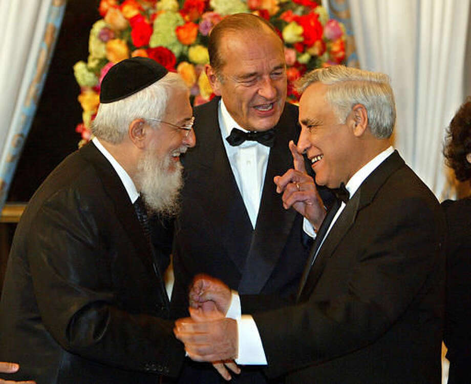 FILE - In this Feb. 16, 2004 file photo, French President Jacques Chirac, center, speaks as Israeli President Moshe Katsav, right, and Grand Rabbi of France Joseph Sitruk, left, exchange greetings at a dinner party given at the Elysee Palace in Paris, on the first day of Katsav's state visit to France. Sitruk, who oversaw a growth in synagogues and Jewish schools, has died after a long illness. He was 71. The French president's office announced Sitruk's death in a statement on Sunday, Sept. 25, 2016. (Jack Guez/Pool Photo via AP)