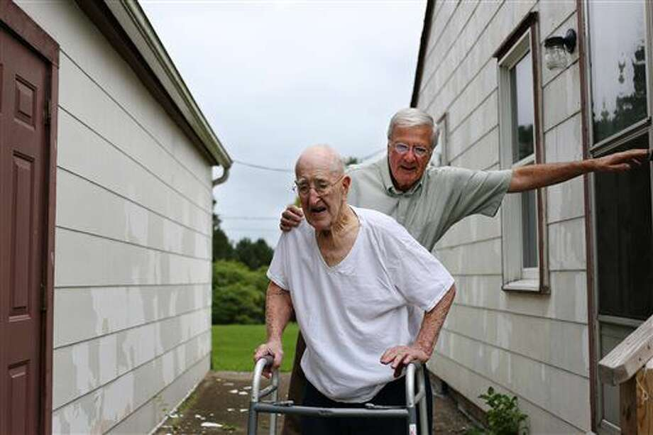 In this Thursday, Sept. 8, 2016 photo, 96-year-old World War II veteran Maynard Bunce is guided down the steps by Jim Bayne at Bunce's home, in Jackson, Mich. The East Jackson High School football team in Jackson is planning to retouch Bunce's home with a fresh coat of paint on Sept. 17 (Samantha Madar/Jackson Citizen Patriot via AP)