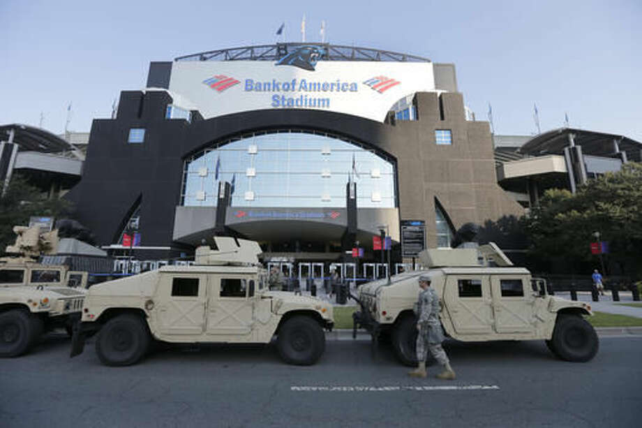 North Carolina National Guard vehicles are parked in front of an entrance to Bank of America Stadium before an NFL football game between the Carolina Panthers and the Minnesota Vikings in Charlotte, N.C., Sunday, Sept. 25, 2016. Increased security is in place for the game after five nights of protests over Tuesday's fatal police shooting of Keith Lamont Scott. (AP Photo/Chuck Burton)