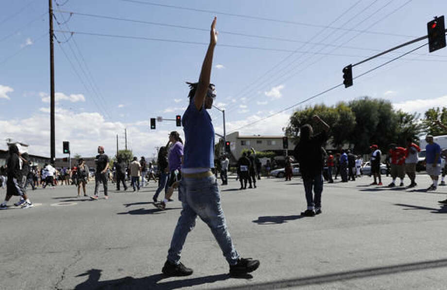 "People block off a street corner during a protest Wednesday, Sept. 28, 2016, in El Cajon, Calif. Dozens of demonstrators on Wednesday protested the killing of a black man shot by an officer after authorities said the man pulled an object from a pocket, pointed it and assumed a ""shooting stance."" (AP Photo/Gregory Bull)"