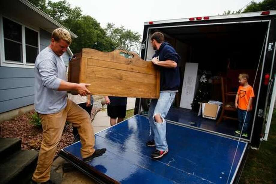 Charley Johnson moves his furniture out of his house as flood waters continue to rise on Friday, Sept. 23, 2016 in Waverly, Iowa. Authorities in several Iowa cities were mobilizing resources Friday to handle flooding from a rain-swollen river that has forced evacuations in several communities upstream (Brian Powers/The Des Moines Register via AP )