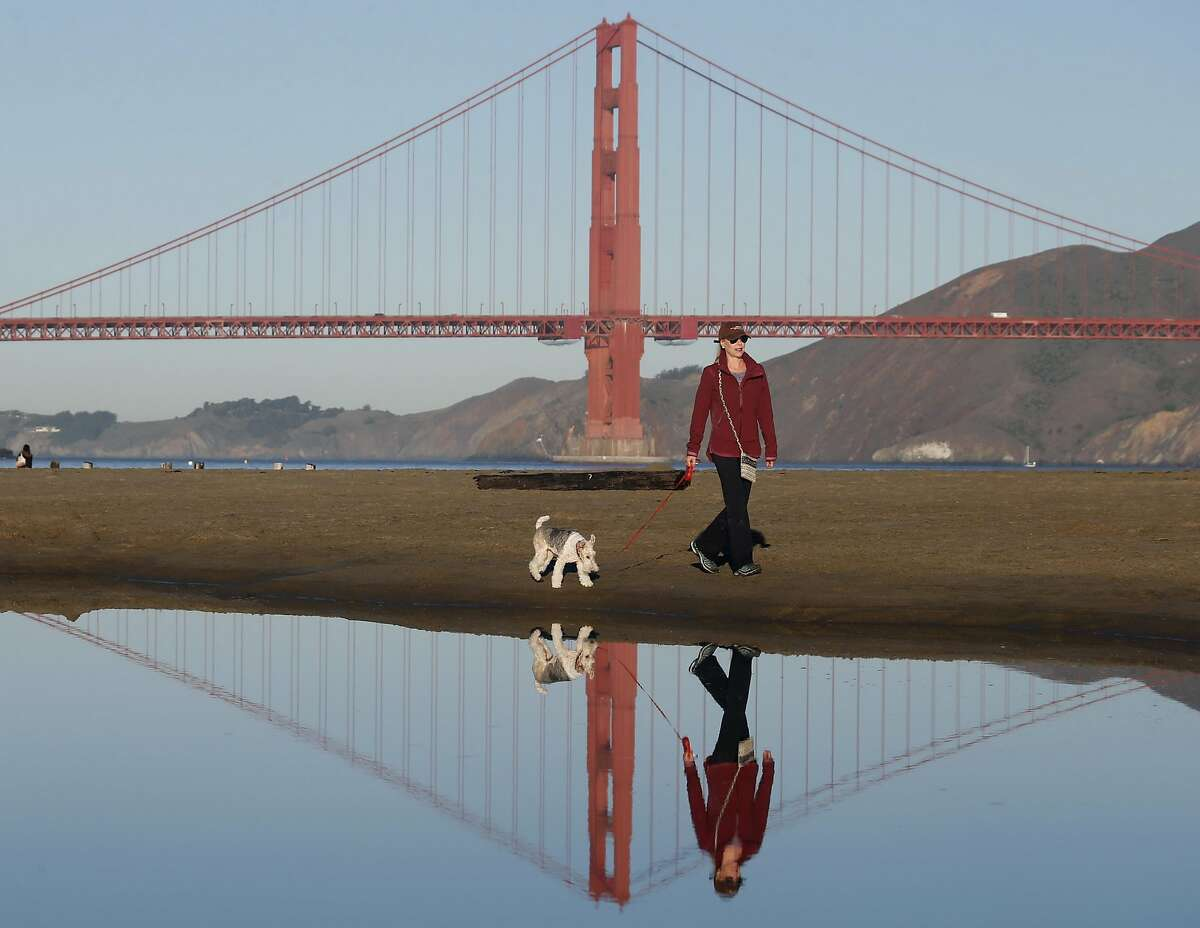 Daphne Stumpel walks on the beach with her dog Gigi at Crissy Field in San Francisco, Calif. on Thursday, Oct. 20, 2016. Forecasters are predicting that La Ni�a conditions may lead to another winter of drier than normal weather.