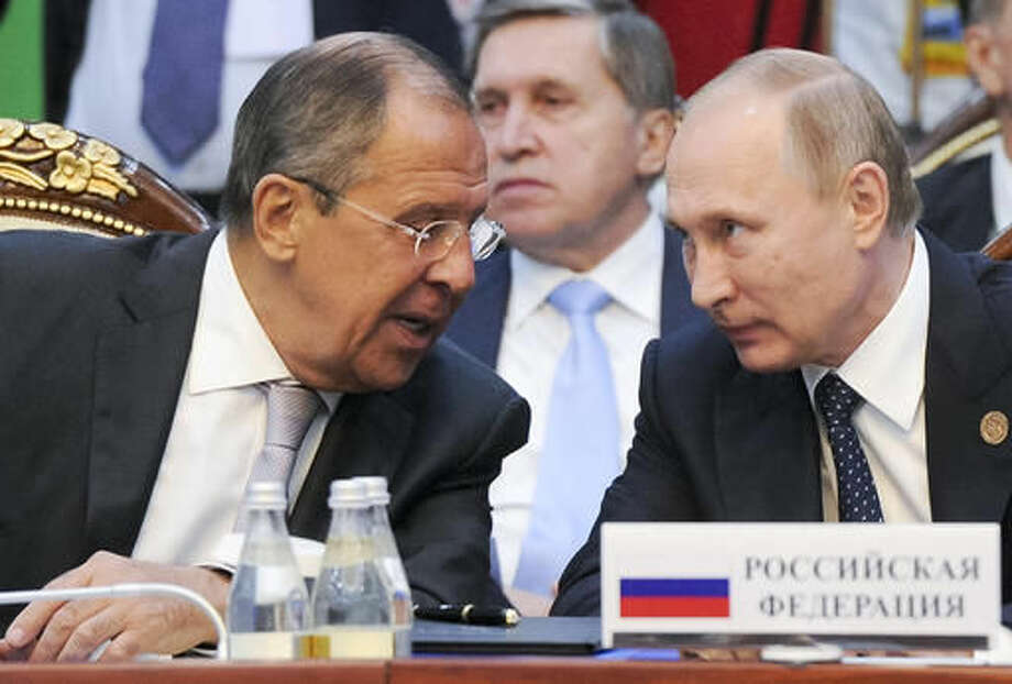 Russian President Vladimir Putin, right, and Russian Foreign Minister Sergey Lavrov speak each other at a CIS (Commonwealth of Independent States, former Soviet republics) summit in Bishkek, Kyrgyzstan, Saturday, Sept. 17, 2016. (Mikhail Klimentyev/Sputnik, Kremlin Pool Photo via AP)