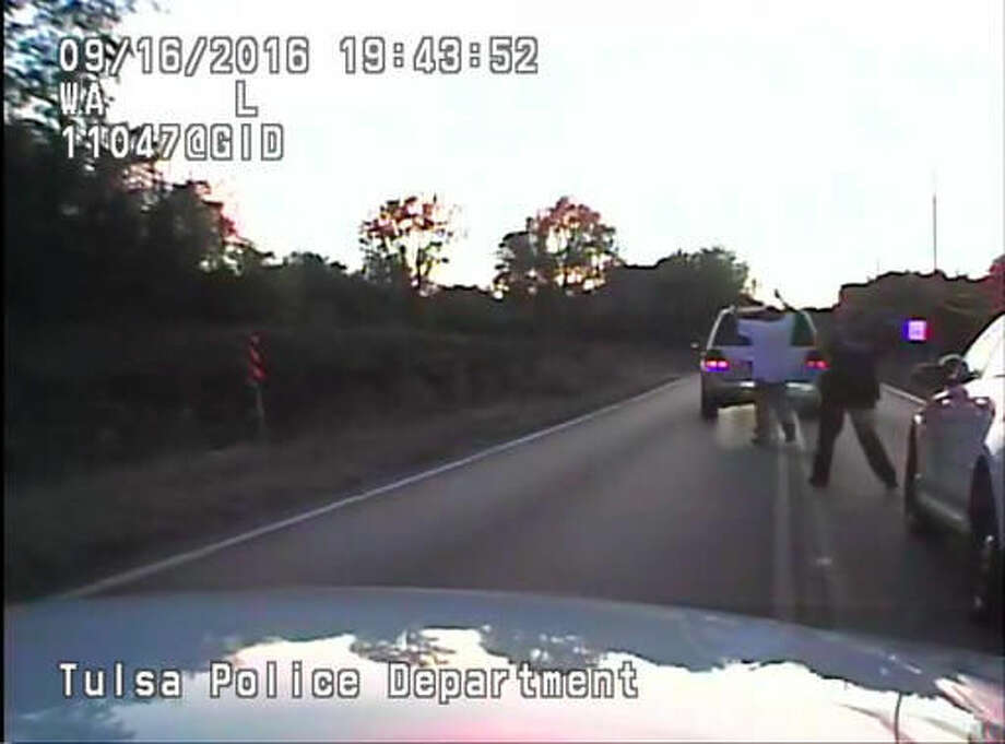 In this image made from a Friday, Sept. 16, 2016 police video, Terence Crutcher, left, is pursued by police officers as he walks to an SUV in Tulsa, Okla. Crutcher was fatally shot Friday after authorities say an officer stopped to investigate the stalled vehicle and Crutcher approached after officers arrived to assist. Crutcher had no weapon on him or in his SUV, Tulsa Police Chief Chuck Jordan said Monday, Sept. 19, 2016. (Tulsa Police Department via AP)
