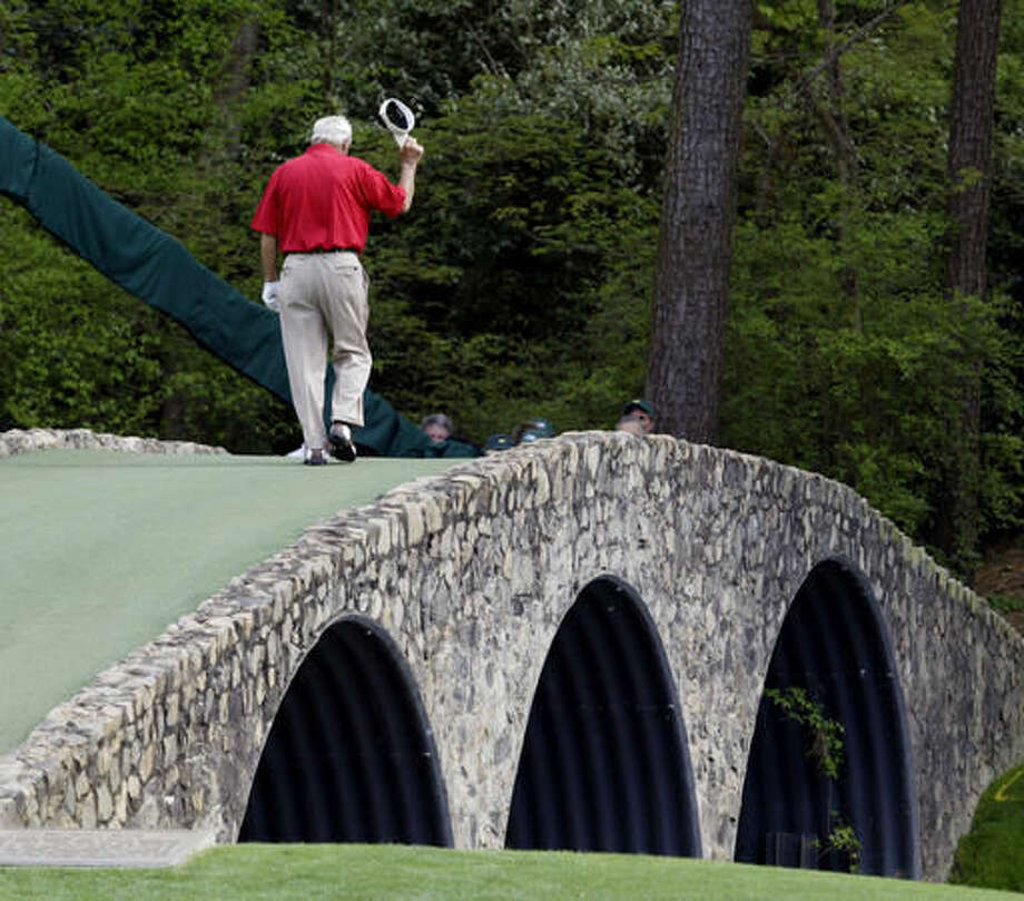 """File- This April 9, 2004, file photo shows Arnold Palmer walking across the Hogan Bridge on the 12th fairway for the final time in Masters competition during the second round of the Masters golf tournament at the Augusta National Golf Club in Augusta, Ga. Palmer, who made golf popular for the masses with his hard-charging style, incomparable charisma and a personal touch that made him known throughout the golf world as """"The King,"""" died Sunday, Sept. 25, 2016, in Pittsburgh. He was 87. (AP Photo/Amy Sancetta, File)"""