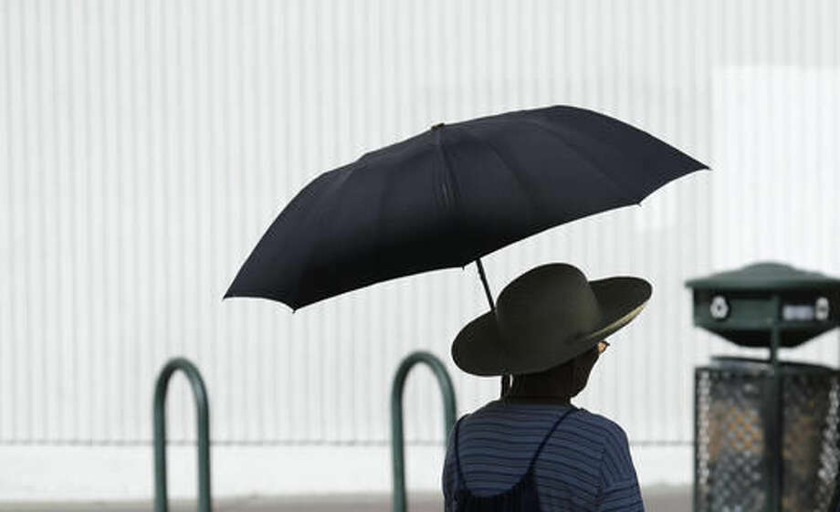 A woman holds an umbrella to shield herself from the sun as she shops in the Chinatown district, Monday, Sept. 26, 2016, in Oakland, Calif. The National Weather Service issued a heat advisory for the Bay Area with record-breaking temperatures and unhealthy air expected all day. (AP Photo/Ben Margot)