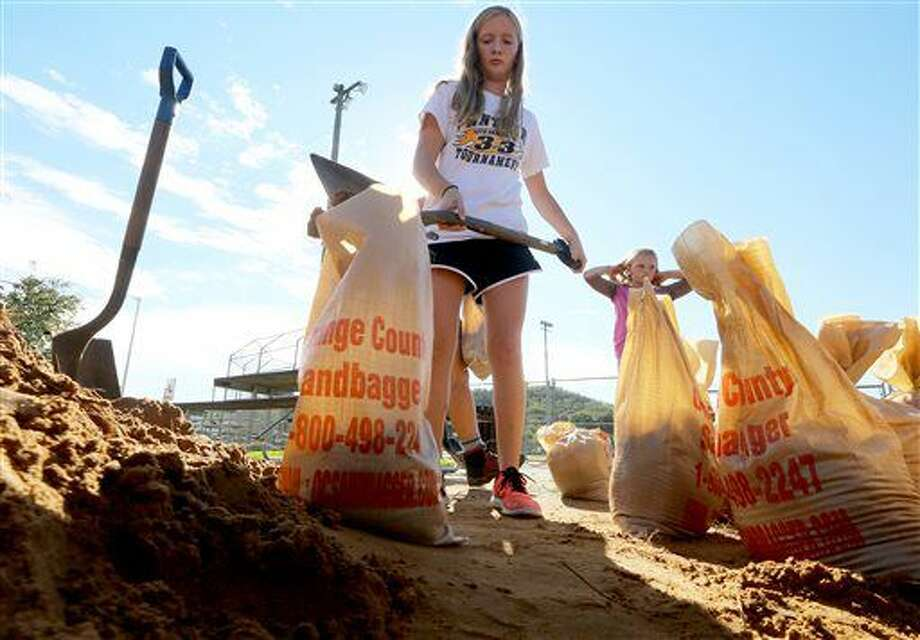 In this Thursday, Sept. 22, 2016 photo, Lexi Mieden fills sand bags for use by residents threatened by rising floodwaters in Richland Center, Wis. Wisconsin Governor Scott Walker declared a state of emergency in multiple counties after authorities said anywhere from five to nine inches of rain fell in the western part of the state this week. (John Hart/Wisconsin State Journal via AP)