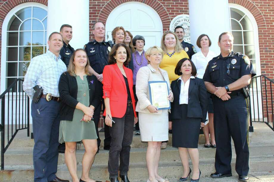 Attending Lynne Vanderslice's Proclamation against Domestic Violence are, front row, from left, police Lt. Stephen Brennan, Domestic Violence Task Force member Sarah Muccio, state Rep. Gail Lavielle, First Selectman Lynne Vanderslice, state Senator Toni Boucher, Chief Bob Crosby. Second row, from left, Sgt. David Hartman, Capt. John Lynch, Chamber of Commerce Executive Director Debra Hanson, task force members Jennifer McNamara and Barbara Holdridge, Domestic Violence Crisis Center attorney advocate Allison Roach, Lt. Rob Cipolla, and Social Services Director Cathy Pierce. Photo: Pat Tomlinson / Hearst Connecticut Media