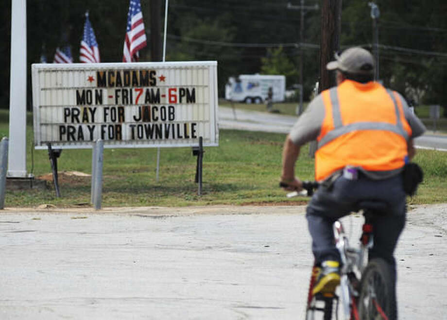 A bicyclist rides past a sign urging prayer for victims of a school shooting in Townville, S.C., on Thursday, Sept. 29, 2016. Authorities say two students and a teacher were wounded by a gunman at an elementary school. (AP Photo/Jay Reeves)