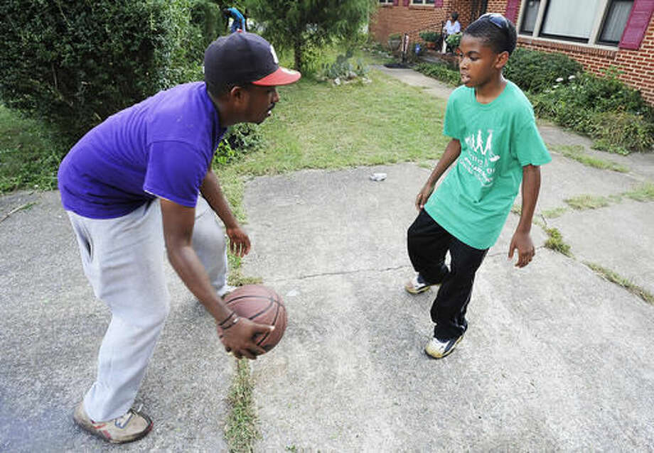 In this photo taken Saturday, Sept. 10, 2016, in Huntsville, Ala., Rodney Smith Jr. and 13-year-old Jarius Smith play basketball after cutting grass for a homeowner while volunteering for Raising Men Lawn Care Service. Founded by Smith last year, the service provides free yard care for the elderly, disabled, single mothers and veterans. Parents sign up youngsters to participate to teach them about volunteering. (AP Photo/Jay Reeves)