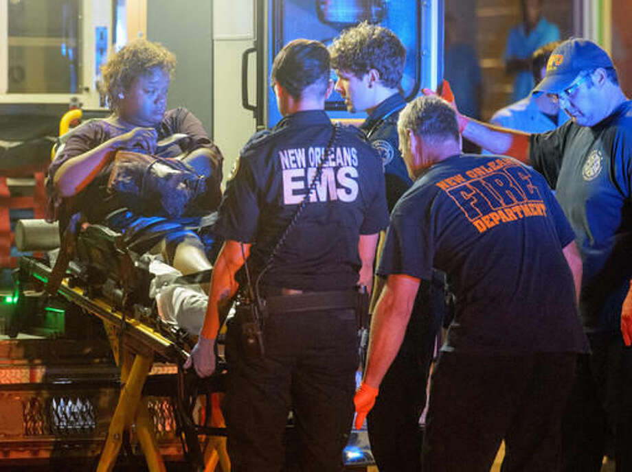 New Orleans Police Department, Fire Department, and EMS personnel respond to an injured woman at the scene of shooting where multiple people were shot, near First and South Derbigny St. in New Orleans, La. Sunday, Sept. 11, 2016. NOPD said they were working a triple shooting in the area. The woman was transported from the scene via ambulance. (Matthew Hinton/The Advocate via AP)