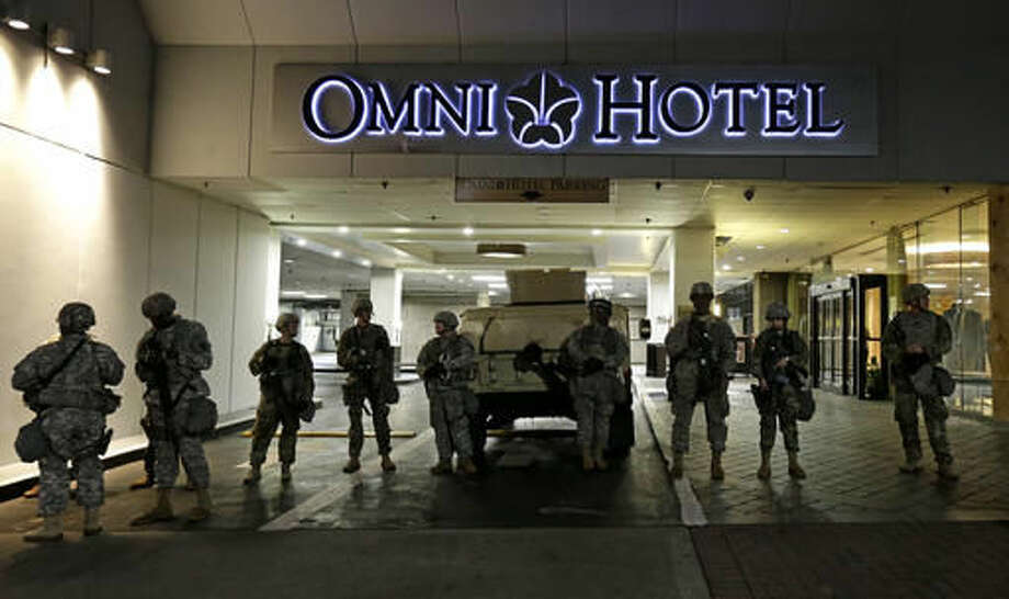 Members of the North Carolina National Guard stand guard outside the Omni Hotel as demonstrators take to the streets following Tuesday's police shooting of Keith Lamont Scott in Charlotte, N.C., Thursday, Sept. 22, 2016. (AP Photo/Gerry Broome)