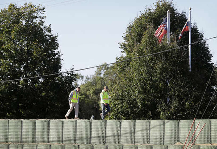 Workers walk across a flood wall made of Hesco barriers near the flood swollen Cedar River, Tuesday, Sept. 27, 2016, in Cedar Rapids, Iowa. An elaborate system of temporary floodwalls largely protected Cedar Rapids homes and businesses Tuesday as the river that runs through the city reached its second-highest peak ever. (AP Photo/Charlie Neibergall)