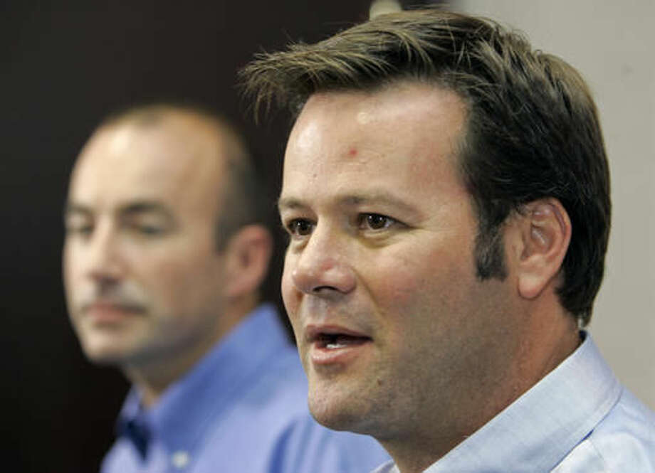 FILE - In this Aug. 8, 2007, file photo, NASCAR racer Robby Gordon, right, answers a question during a news conference in Charlotte, N.C. Police said a husband and wife were found dead inside a home Wednesday, Sept. 14, 2016, in Orange, Calif., and a neighbor said they were Gordon's father and stepmother. (AP Photo/Chuck Burton, File)