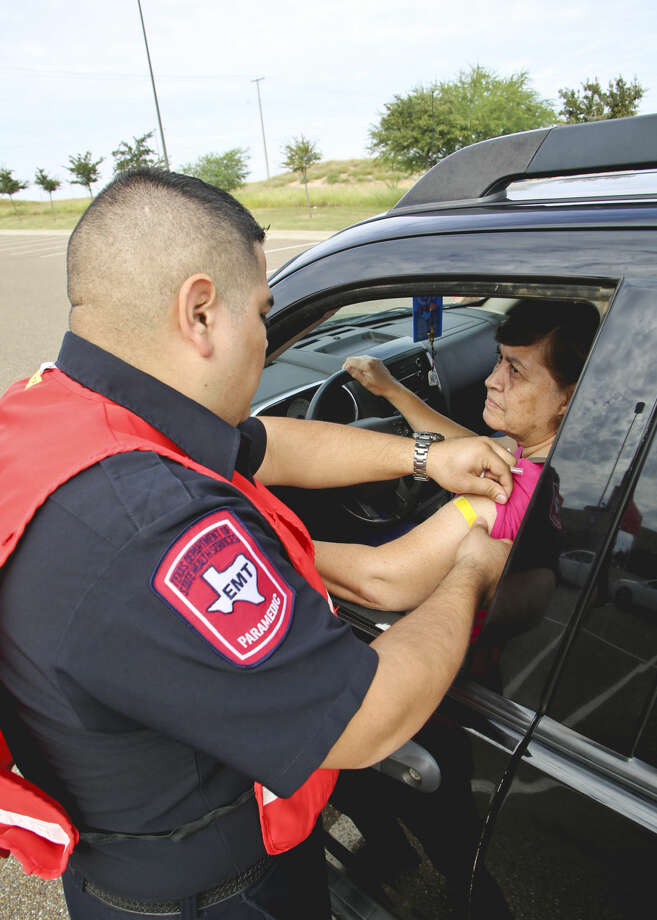 In this 2013 photo, Rosa Maria Vedia gets a flu shot from EMT Jose Cervantes during the influenza shot drive-thru at the LEA.