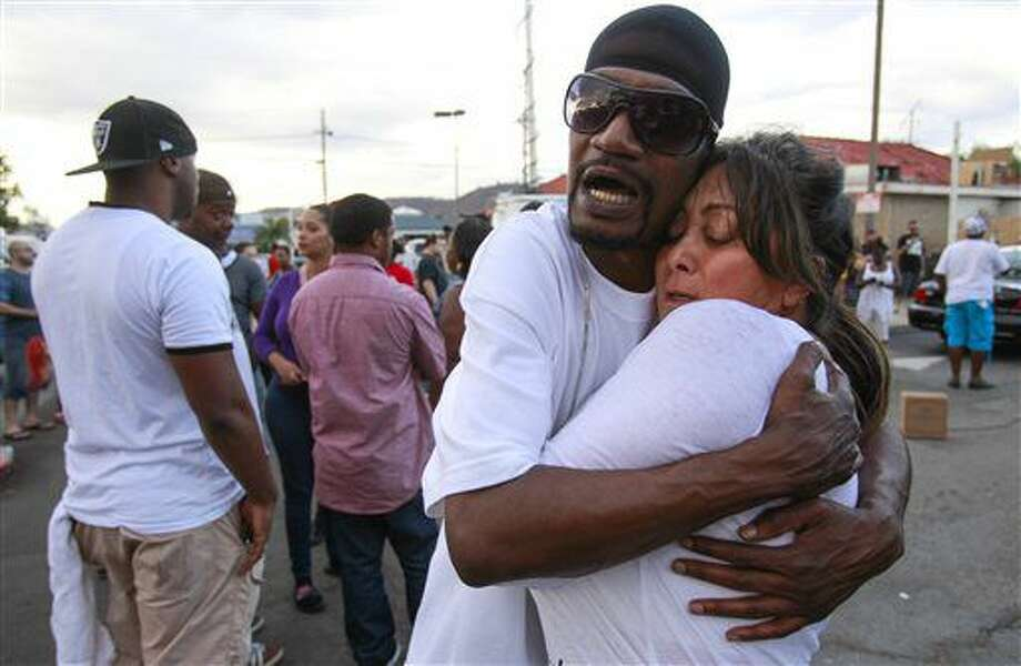Shawn Letchaw hugs a woman named Marie, who didn't give her last name, at the scene where a black man was shot by police earlier in El Cajon, east of San Diego, Calif., Tuesday, Sept. 27, 2016. (Hayne Palmour IV/The San Diego Union-Tribune via AP)