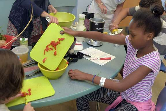 Serenity Sumler, 10, cuts strips of red pepper and places them in a bowl to add to the potato dish. Danielle Cook, mother of a cancer survivor, who created the program, Happily Hungry, helps teach children with cancer at Sinai Hospital in Cockeysville, Md., how to cook meals they will enjoy.