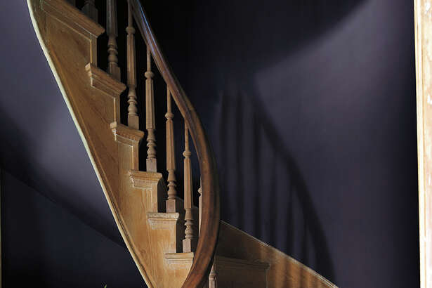 """The walls along this staircase are painted in Benjamin Moore's """"Shadow,"""" a very dark purple that is the company's 2017 Color of the Year."""