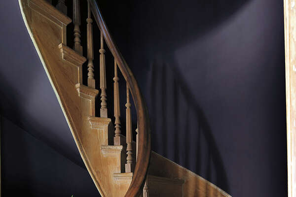 "The walls along this staircase are painted in Benjamin Moore's ""Shadow,"" a very dark purple that is the company's 2017 Color of the Year."