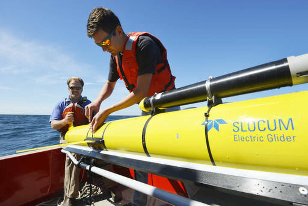 In this Sept. 2, 2016 photo, Woods Hole Oceanographic Institution engineers Sean Whelan, left, and Patrick Deane release a Slocum glider into the waters south of Martha's Vineyard, Mass. to monitor anticipated changes in the ocean during the passage of tropical storm Hermine. The underwater drones, or gliders as they are known, collect data that scientists say will help them better understand what sustains and strengthens hurricanes and tropical storms. (Ken Kostel/Woods Hole Oceanographic Institution via AP)