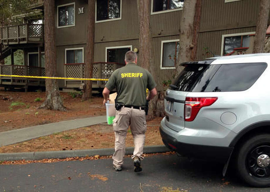Investigators are seen at the apartment complex that has been tied to Arcan Cetin, the suspected Cascade Mall shooter, in Oak Harbor, Wash., Sunday, Sept. 25, 2016. Authorities carried boxes from a rear, upstairs apartment in the four-unit building. (AP Photo/Martha Bellisle)