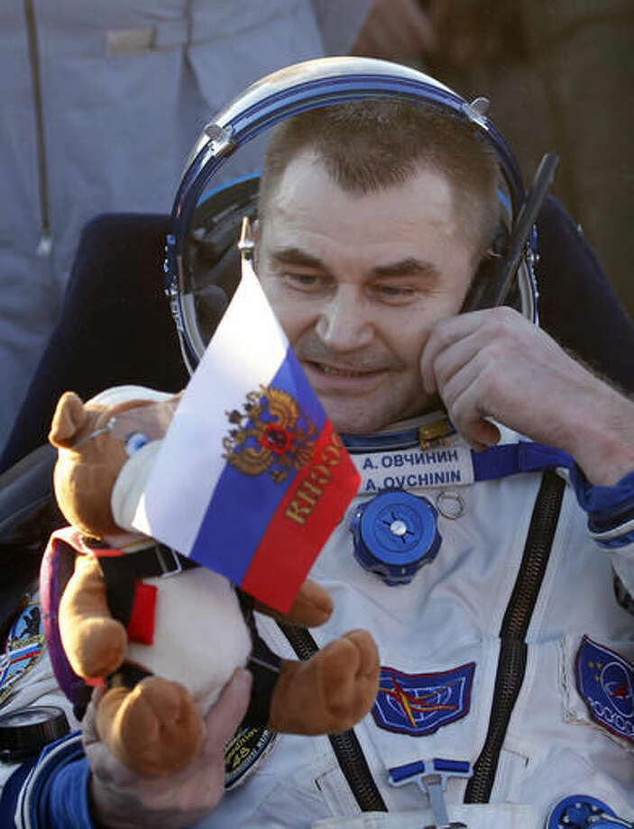 Russian cosmonaut Alexey Ovchinin holds Russian flag and a toy bear, as he uses a satellite phone after landing in a remote area near the town of Zhezkazgan, Kazakhstan, Wednesday, Sept. 7, 2016. The record-setting American and two Russians landed safely back on Earth Wednesday after a six-month mission aboard the International Space Station. (Maxim Shipenkov/Pool Photo via AP)