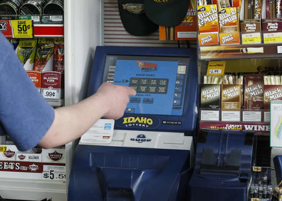 FILE--In this March 5, 2015, file photo, an employee operates the Idaho Lottery machine at On The Fly Gas Mart on in Boise, Idaho. Idaho State Lottery officials are asking potential vendors to provide information on how they would offer Keno, simulated racing, fantasy sports and other illegal gambling games when they bid on a lucrative decade-long contract--gambling companies hoping to be the next Idaho State Lottery provider have until the end of Friday, Sept. 9, 2016, to turn in their bids. (AP Photo/Otto Kitsinger, file)