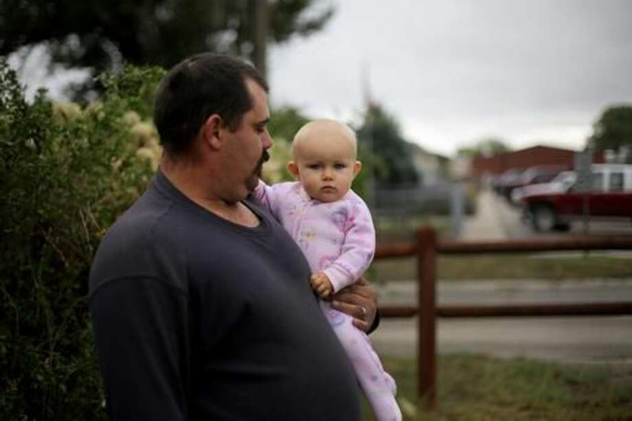 In this Sept. 13, 2016 photo, Mark McMurray stands with his 10-month-old daughter Piper at his home near Midwest School in Midwest, Wyo. McMurray, who works in the oil business, says he isn't too concerned about the benzene and carbon dioxide levels around Midwest. (Dan Cepeda/The Casper Star-Tribune via AP)