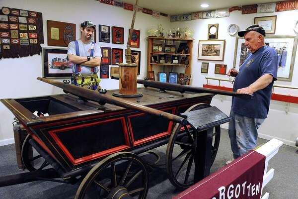 Nick Bennette, 34, a firefighter/ engineer and Richard Reynolds, 72, a retired fire chief, both with the Bethel Volunteer Fire Department, look over a 1815 hand pumper cart which is in the Bethel Fire Museum, Wednesday, Oct. 19, 2016.