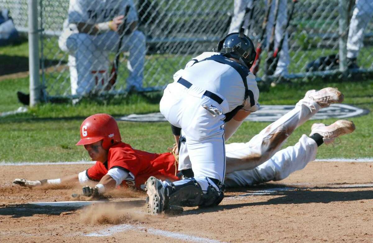 Yuta Okazaki of Greenwich High School is out at home plate as Staples catcher, Grant Moss, puts the tag on him during the top of the first inning when Okazaki attempted to take home on a play to another base, at Staples HS, Westport, Conn., May 13, 2010.