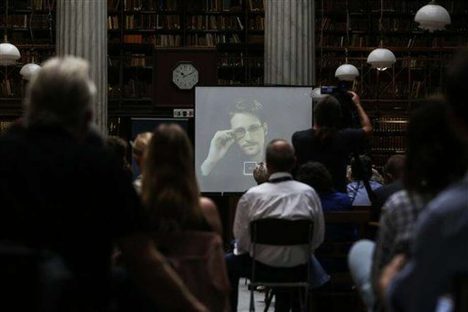 National Security Agency leaker Edward Snowden speaks via video link during the Athens Democracy Forum, organised by the New York Times, at the National Library in Athens, Friday, Sept. 16, 2016. Snowden, in exile in Moscow after leaking U.S. National Security Agency documents, said Friday he intends to vote in the U.S. presidential election, but did not say which candidate he favors. (Kostas Baltas, InTime Sports via AP)