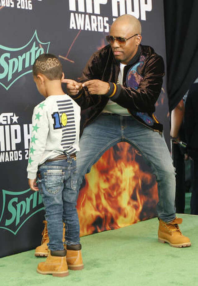 Hip-hop artist Consequence points to his son Caiden, left, with his name written in his haircut, on the green carpet for the BET Hip Hop Awards in Atlanta, Saturday, Sept. 17, 2016. (AP Photo/Tami Chappell)