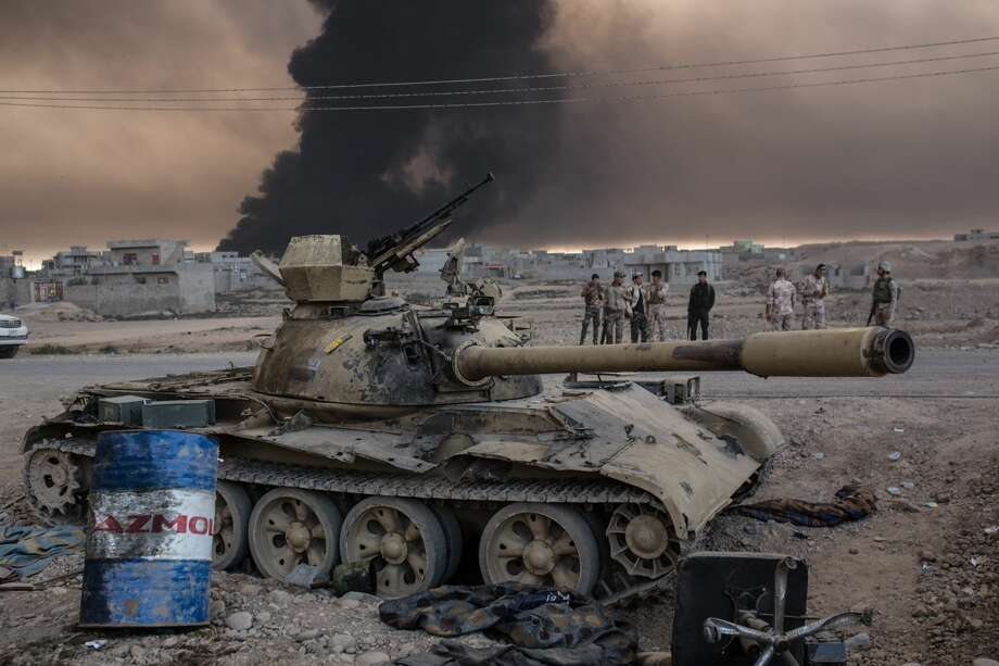 Iraqi soldiers stand next to a tank as smoke rises from the Qayyarah area, some 60 kilometres (35 miles) south of Mosul, on October 19, 2016, during an operation against Islamic State (IS) group jihadists to retake the main hub city. In the biggest Iraqi military operation in years, forces have retaken dozens of villages, mostly south and east of Mosul, and are planning multiple assaults for October 20. Photo: YASIN AKGUL/AFP/Getty Images