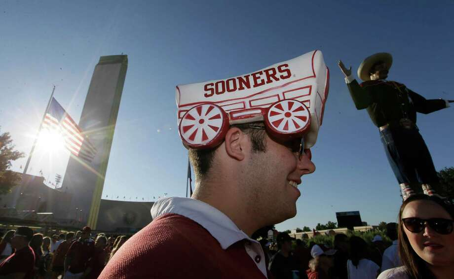 FILE - In this Oct. 8. 2016, file photo, Oklahoma fan Grayson Niemeyer wears a hat at the state fair before an NCAA college football game between Texas and Oklahoma in Dallas. Now that the Big 12 has decided to stay at 10 schools, it's time to figure out whether or not to split up _ into football divisions. If so, how will the teams be divided? The league, which will keep its round-robin schedule, has to determine who will play in its championship game that returns next season. (AP Photo/LM Otero, File) Photo: LM Otero, STF / Copyright 2016 The Associated Press. All rights reserved.