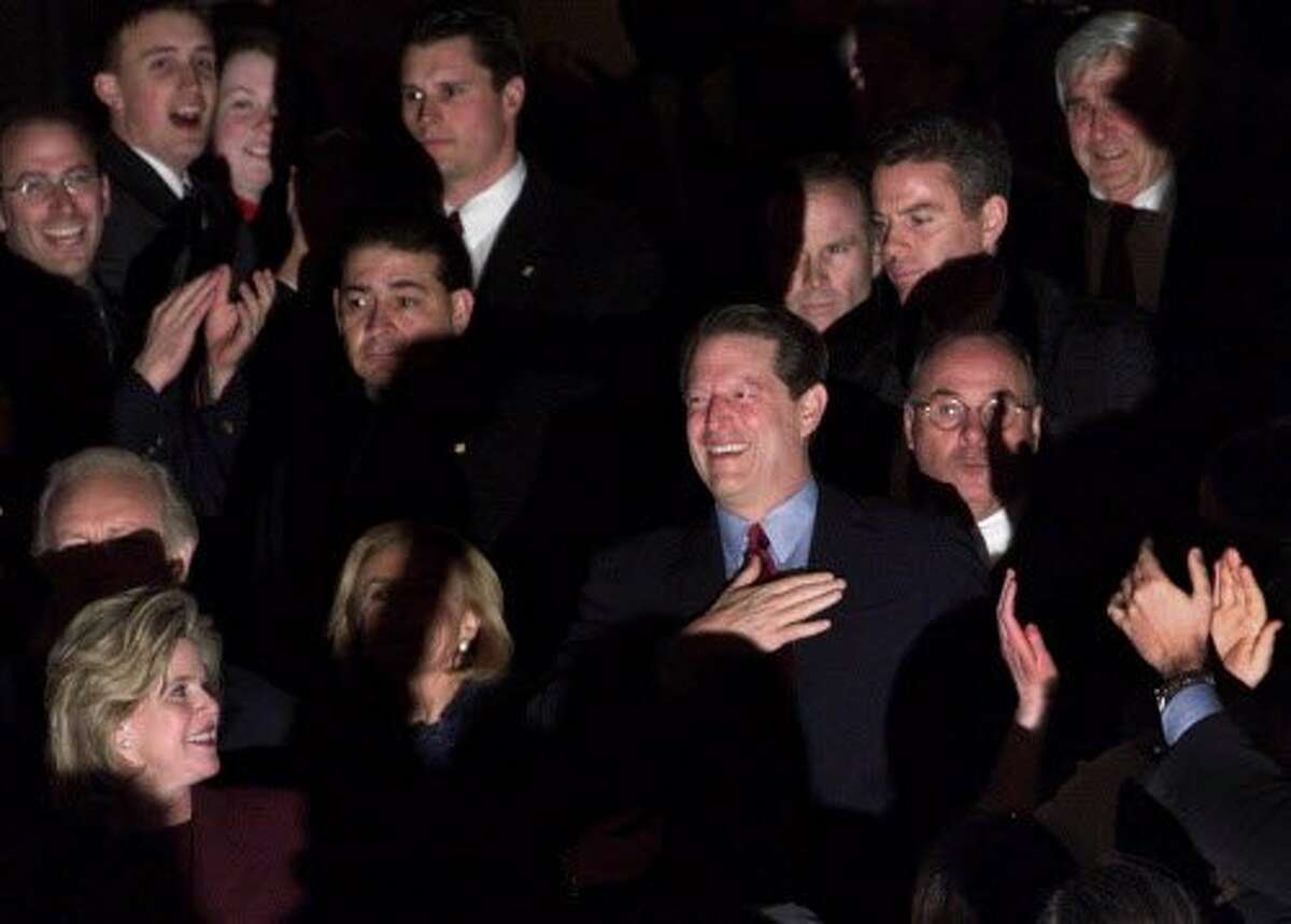 Vice President Al Gore is greeted by applause from supporters as his wife, Tipper, bottom left corner, watches as they leave the Old Executive Office building following his concession speech Wednesday, Dec. 13, 2000, in Washington. (AP Photo/Victoria Arocho)