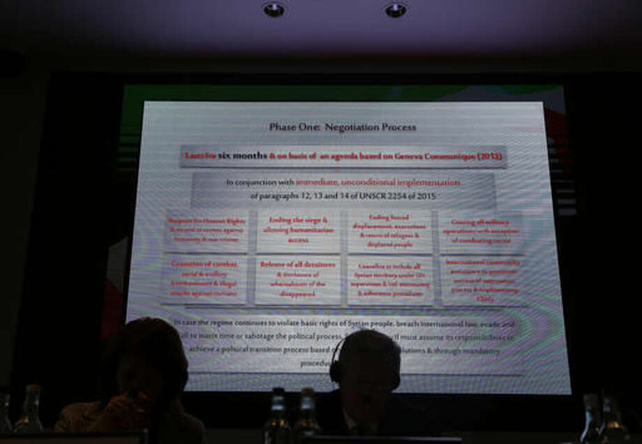 A slide of the transition plan displayed on a large screen is described by Riyad Hijab, General Coordinator of the High Negotiation Committee at the launch of Syrian High Negotiations Committee Transition Plan at the International Institute for Strategic Studies in London, Wednesday, Sept., 7, 2016. Syrian opposition leaders unveiled plans for a political transition ahead of a Friends of Syria meeting in London. The High Negotiations Committee scheme is set to be made public Wednesday in a session at the International Institute for Strategic Studies. (AP Photo/Alastair Grant)