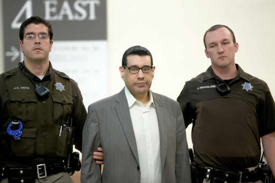 Anthony Garcia, center, is led by sheriff's deputies at the Douglas County Court in Omaha, Neb., Monday, Sept. 26, 2016, following a day of jury selection for his trial. Garcia, a former doctor, is accused of killing four people with ties to an Omaha medical school that fired him in 2001. (AP Photo/Nati Harnik)