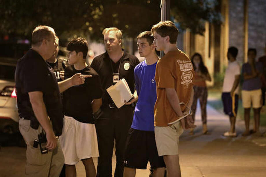 Daniel Hamilton Magee, second left, stands with Austin Police Department officers after being arrested late Sunday night, Sept. 11, 2016 in Austin, Texas. Magee, who isn't a UT student, was charged with aggravated assault after a security guard was injured in a shooting at the the Sigma Chi fraternity house. (Daulton Venglar/The Daily Texan via AP)