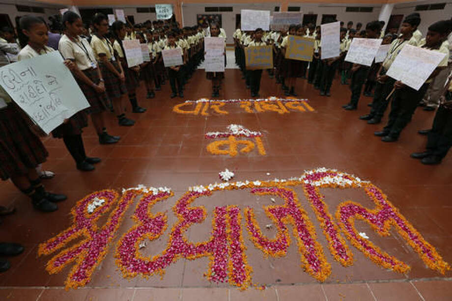 """Indian students hold placards and stand near a formation of flowers that read """"tribute to brave martyrs"""" as they pay tribute to the Indian soldiers killed in the Sunday attack on army base in Indian-controlled Kashmir early Sunday, at a school in Ahmadabad, India, Monday, Sept. 19, 2016. Suspected rebels using guns and grenades sneaked into a crucial army base in Indian-controlled Kashmir early Sunday and killed at least 17 soldiers in the deadliest attack on a military base in the disputed Himalayan region in recent years, the army said. (AP Photo/Ajit Solanki)"""