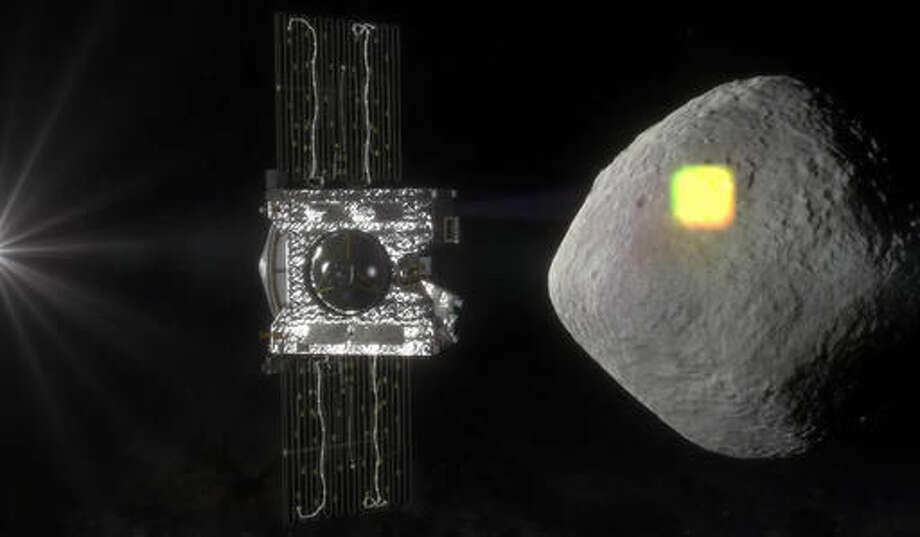This artist's rendering made available by NASA in July 2016 shows the mapping of the near-Earth asteroid Bennu by the OSIRIS-REx spacecraft. The spacecraft will spend a year surveying Bennu before collecting a sample that will be returned to Earth for analysis. (NASA/Goddard/University of Arizona via AP)