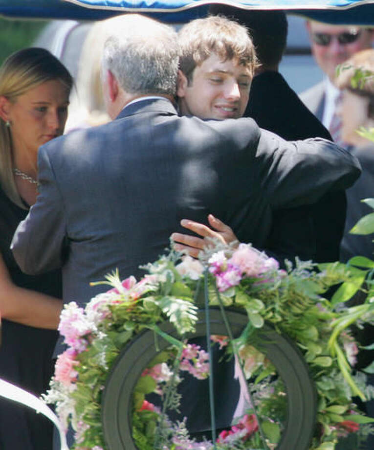 FILE - In this June 29, 2006, file photo, John Ramsey hugs his son, Burke, facing camera, at the graves of his wife, Patsy, and daughter JonBenet, during services for his wife at the St. James Episcopal Cemetery in Marietta, Ga.